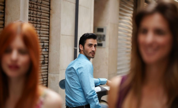 Chico joven con camisa azul se queda mirando a dos mujeres jóvenes, una castaña y otra pelirroja, mientras caminan.