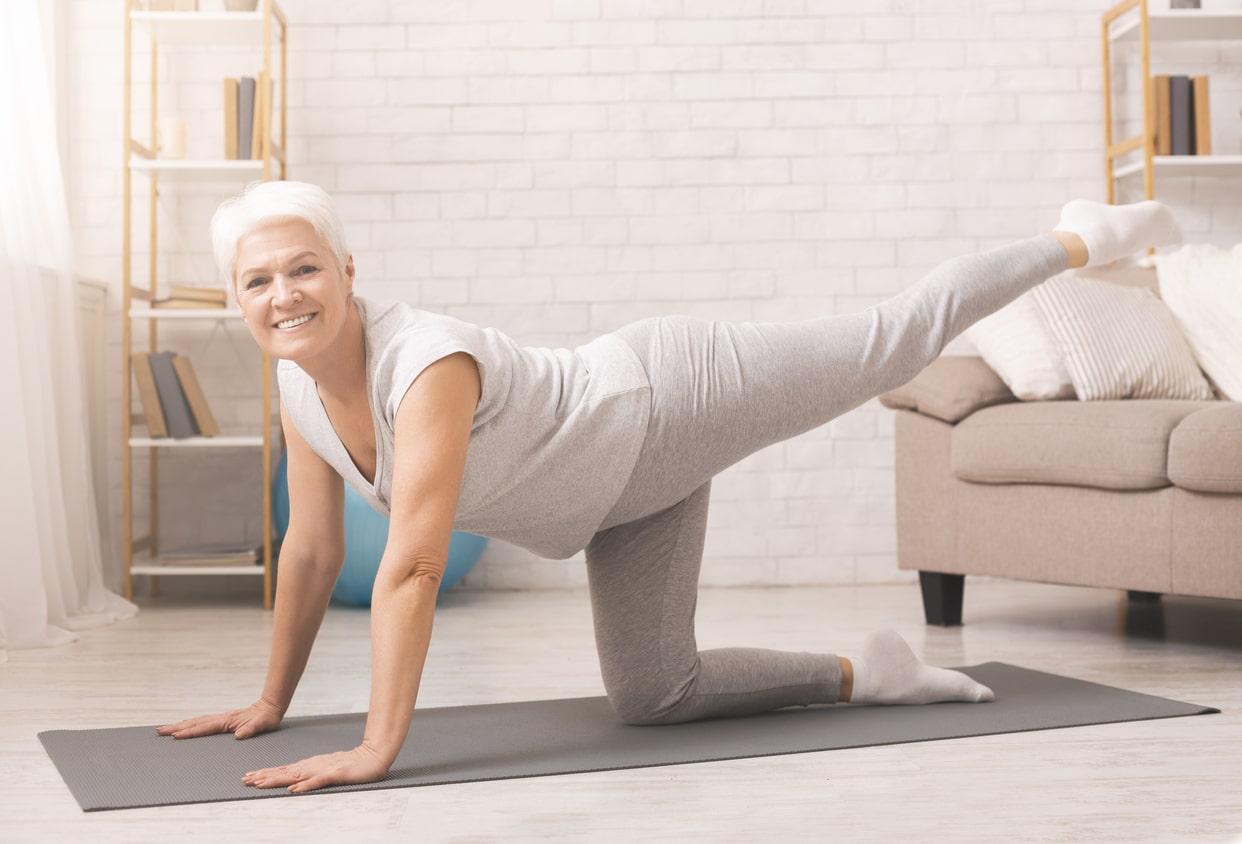 Mujer haciendo ejercicio de patada hacia arriba en el piso para eliminar gordito debajo de los glúteos