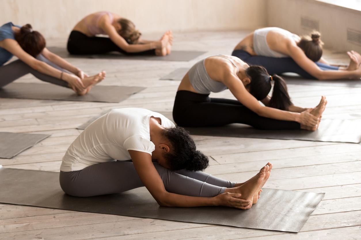 Clase de yoga realizando estiramiento para mejorar circulación