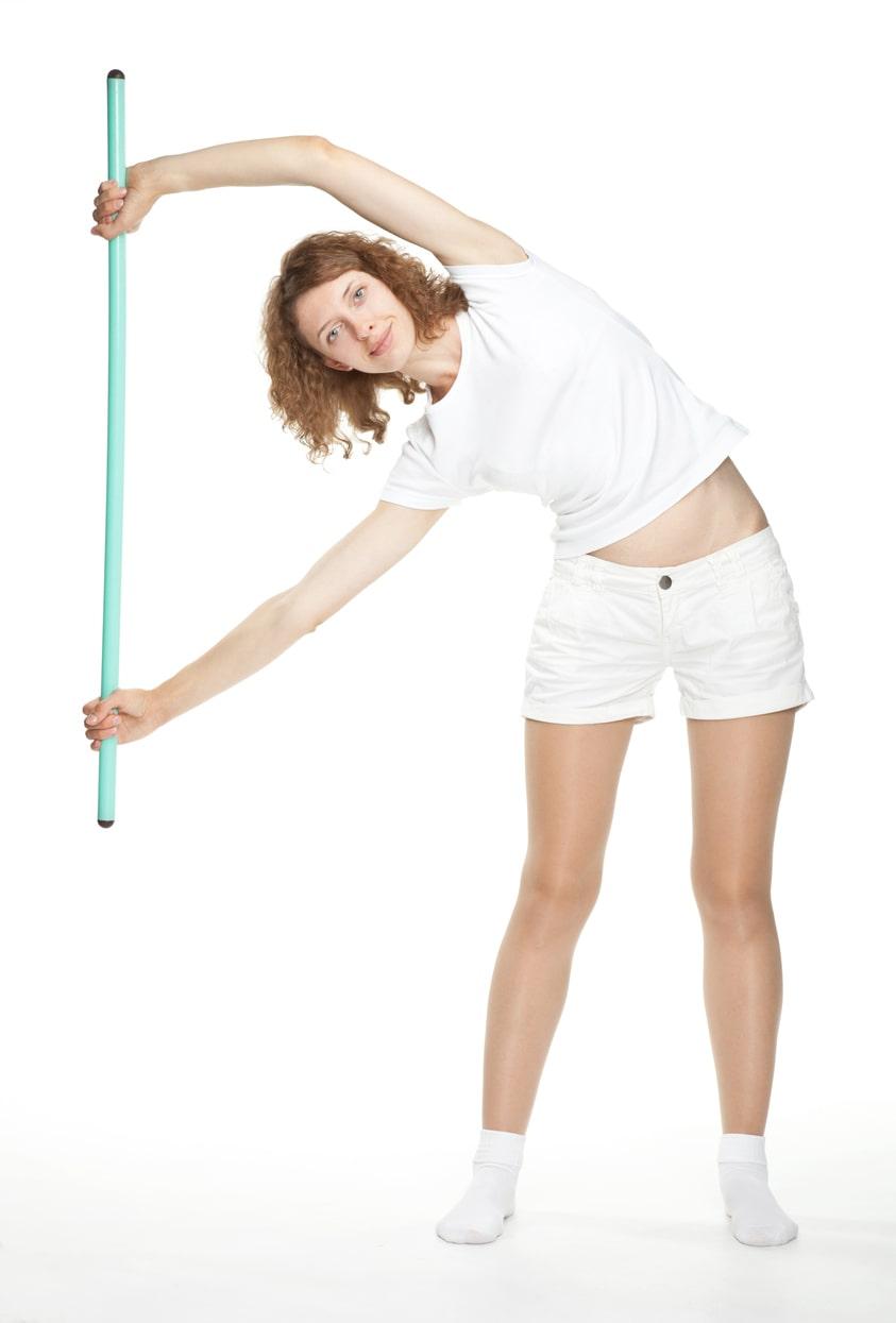 Mujer haciendo flexión lateral con ayuda de un palo de escoba