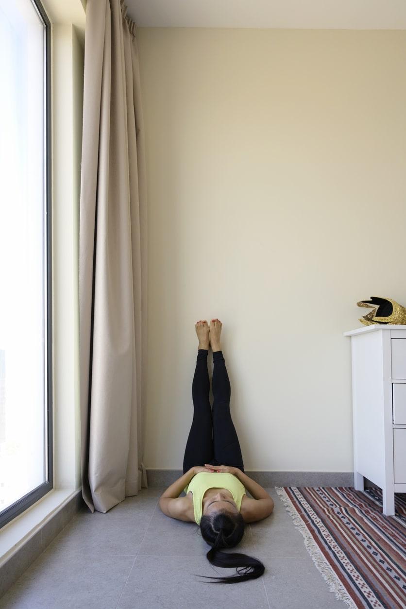 Mujer con piernas apoyadas sobre la pared, preparándose para ejercicio