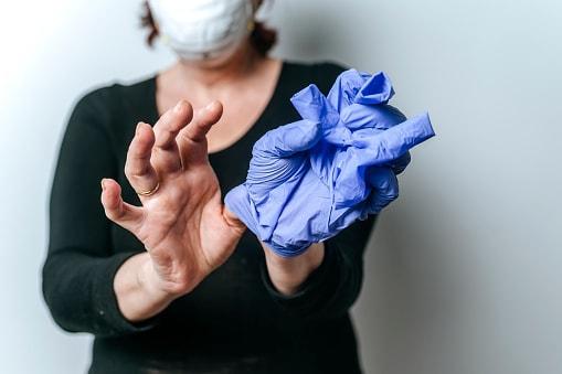 Mujer quitándose los guantes desechables para protegerse del covid