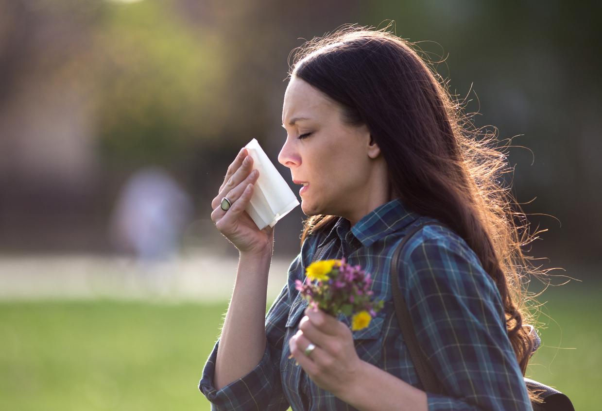 Mujer estornudando por alergia