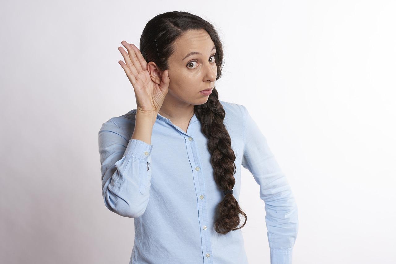 Mujer poniéndose la mano detrás de la oreja para escuchar