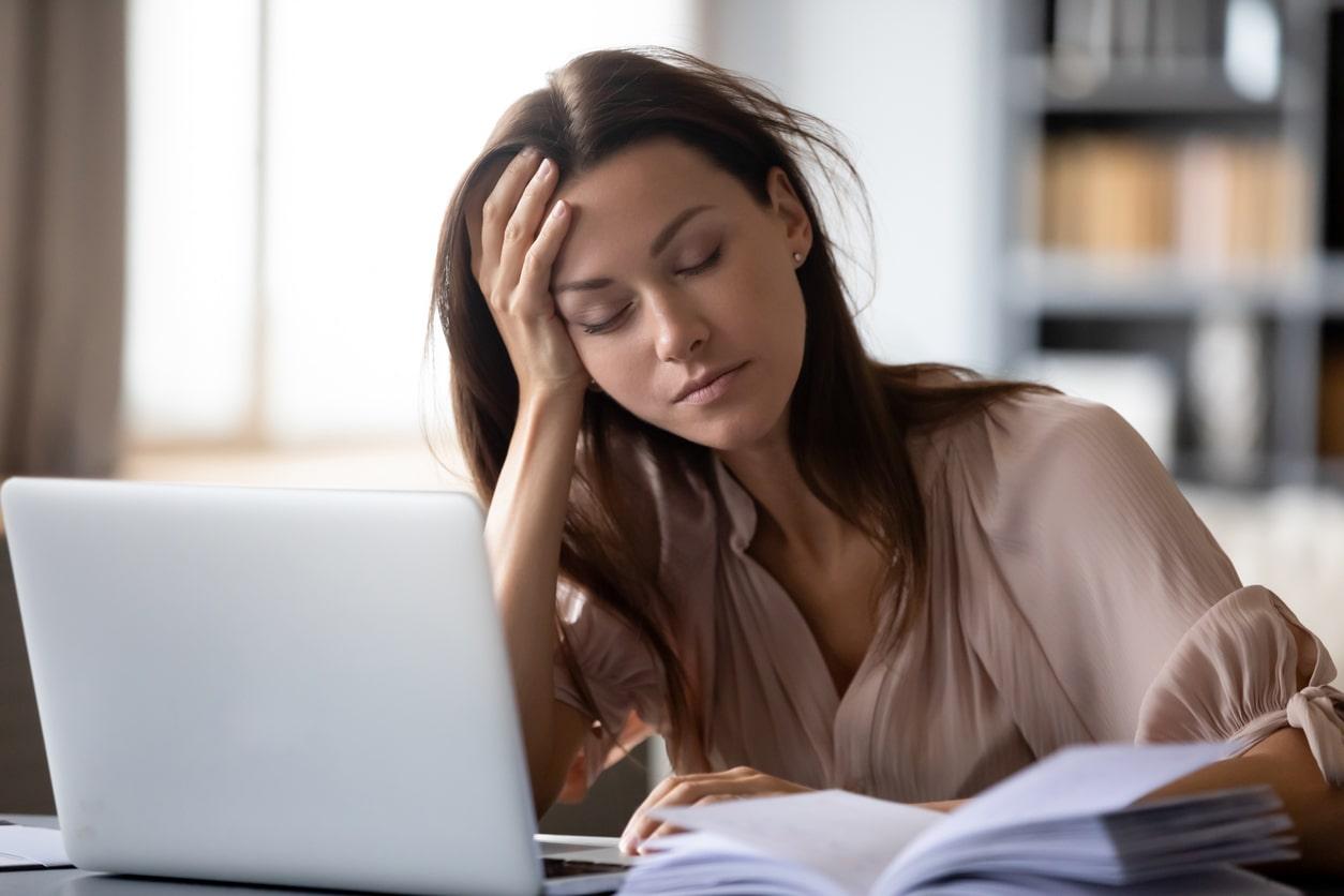 Mujer durmiendo frente a la computadora porque una noche antes tuvo insomnio