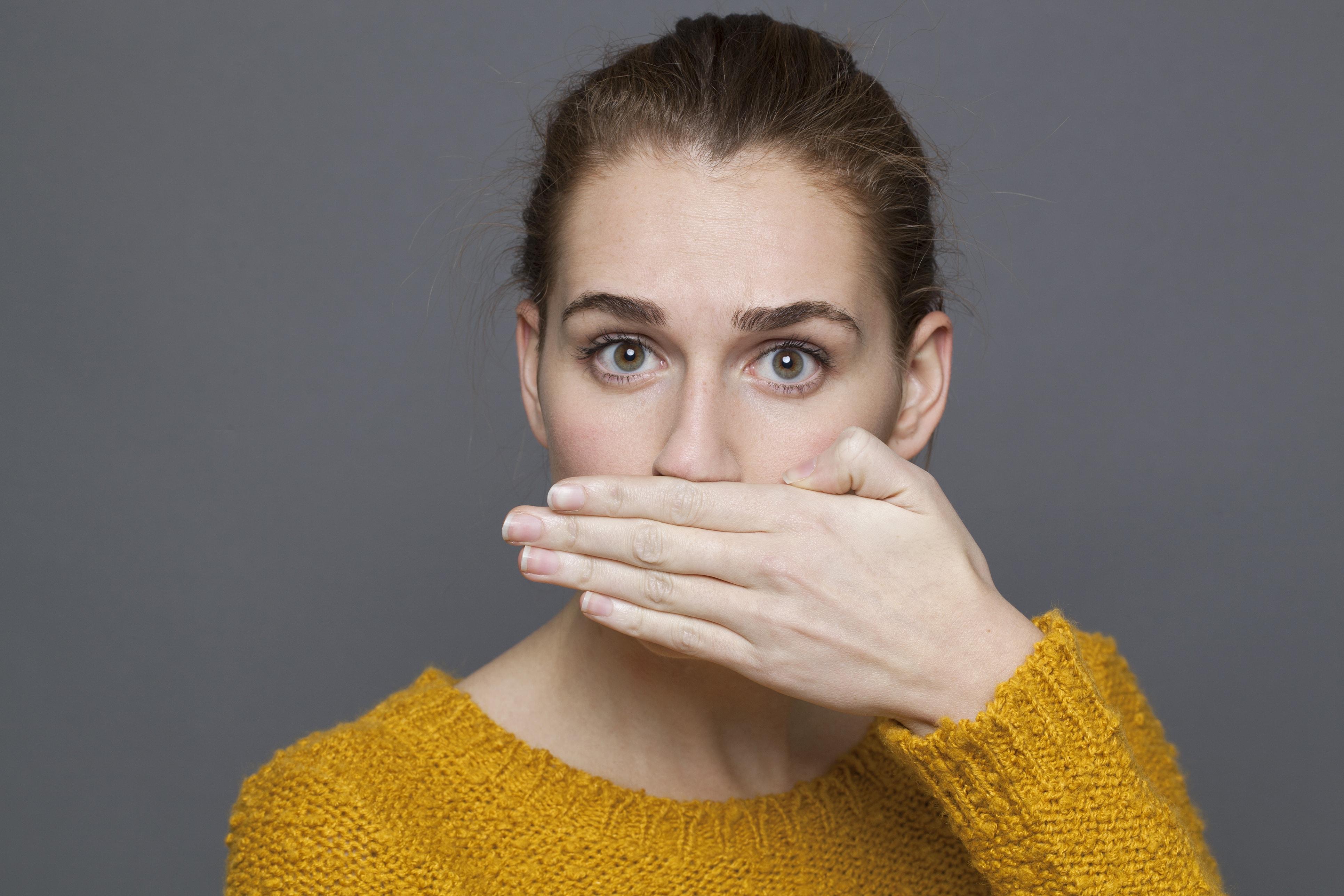 Mujer tapándose la boca con pena