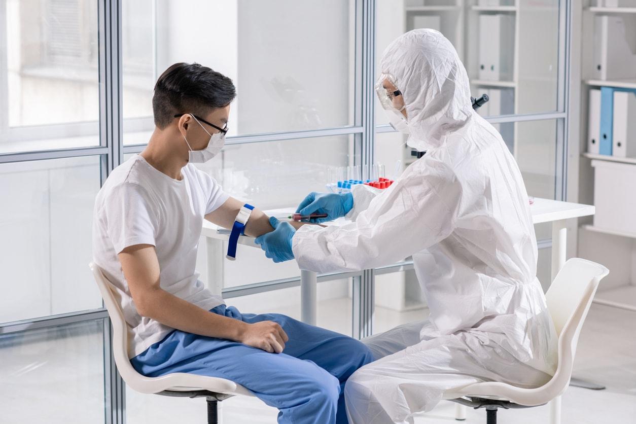 Médico con traje de protección tomando muestra de sangre covid19