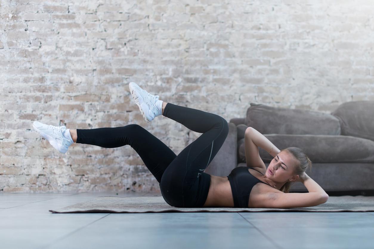 Mujer haciendo abdominales inversas con bicicleta para marcar abdomen