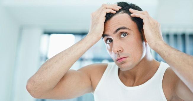 Los cabellos graso cerca de las raíces y las vitaminas secas sobre las puntas