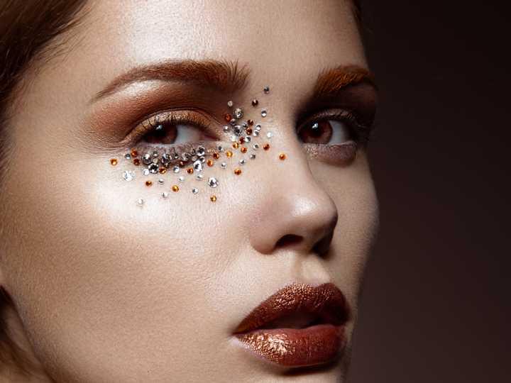 Mujer con gemas en su maquillaje, tendencia para el 2021